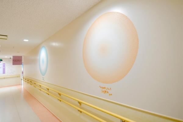 リハビリ室に続く廊下に描かれたGOMA氏による光の絵。細かい色の粒でできている