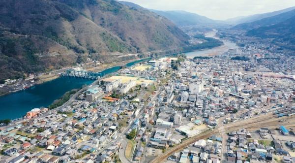 空から見た三好市。手前左から奥中央に向けて流れているのが吉野川。国土交通省による「日本一の清流」にも複数回選ばれている。激流の個所もあり、2015年には日本で初めてラフティングの世界大会が開かれた(写真提供:池田博愛会)