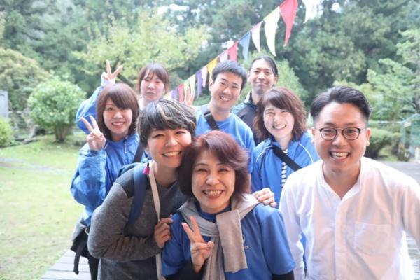 池田博愛会でMEUTRALプロジェクトを推進している岡千賀子さん(写真手前中央)。2019年に開催した「MEUTRAL FESTIVAL 2019 – 秘境のフリーフェス」での一コマ。スタッフやイベント登壇者らと共に。このイベントは音楽フェスや移住者との交流、福祉分野のキーパーソンによるトークセッションなど、さまざまな要素を入れ込んで開催した(写真提供:池田博愛会)