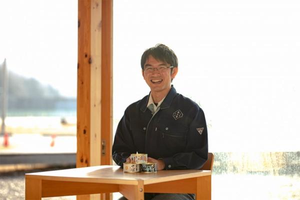 震災から10年、40歳になった松友さんの近影。前にあるのは金華さばなど木の屋石巻水産の定番缶詰シリーズの一部(写真提供:木の屋石巻水産)