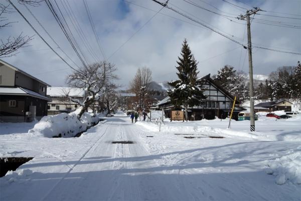 白馬岩岳エリアの一画、雪に覆われた新田地区の街並み。通り沿いに、既存の建物をリノベーションした6棟が並ぶ(写真:守山 久子)