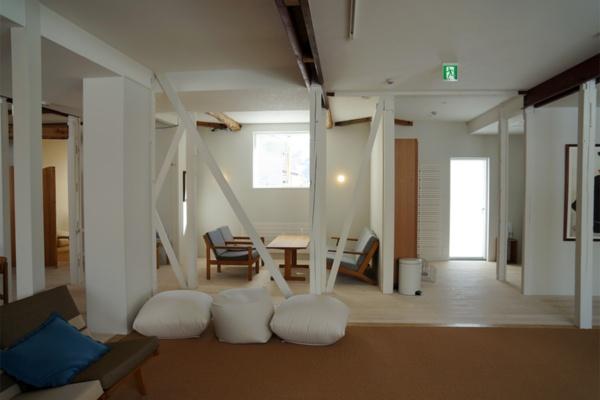 haluta hakubaの1階ラウンジ。民宿を改装し、8室の客室と石風呂のミスト浴などを用意した。館内には北欧のビンテージ家具を配している。改修設計はハルタ建築設計事務所(写真:守山 久子)