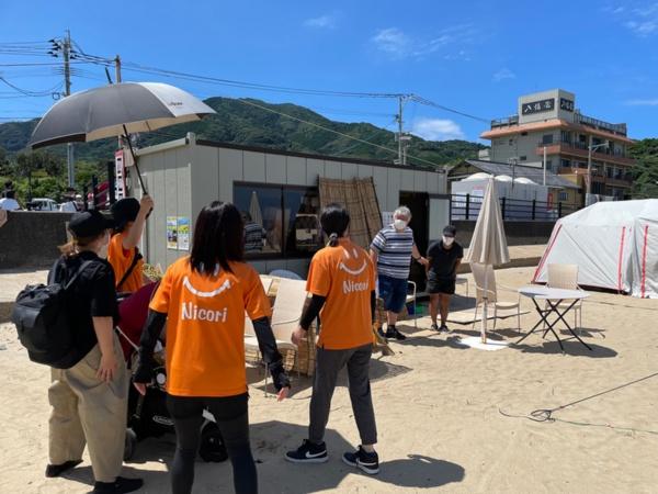 海岸沿いの駐車場にバギーで乗降できるスペースを確保してくれたり(上)、テントを貸したりしてくれるまちの人に挨拶(下)(写真:唐松奈津子)