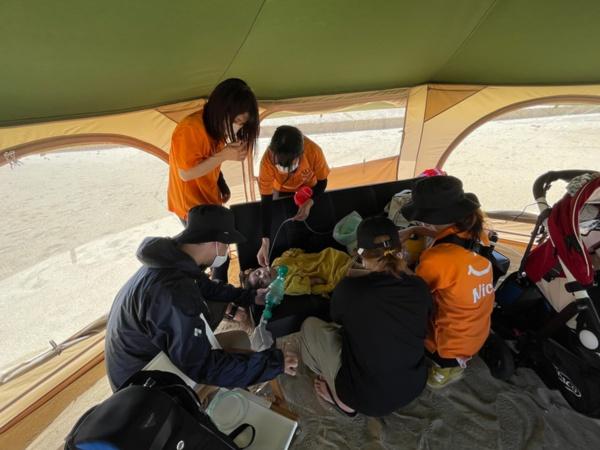 呼吸器があるため、着替えも大人4人がかり(上)。看護師とヘルパーで機器を分担して携帯しながら海辺で記念撮影(下)(写真:唐松奈津子)