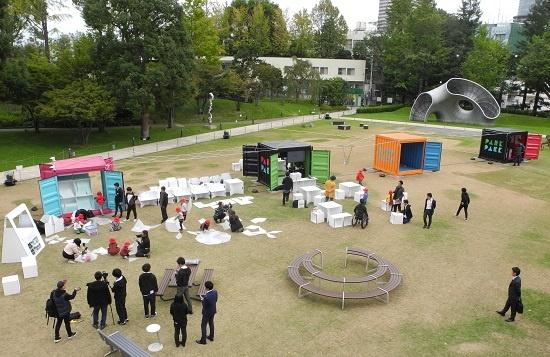 (写真1)東京ミッドタウンの芝生広場に出展された「PARK PACK」。4つのコンテナが「みらいの公園」の舞台装置を提供する(写真:茂木俊輔)