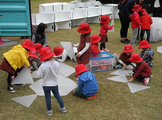 (写真3)子どもたちが手に取る三角形の「モジュール」は川上産業のプチロイド製。日建設計と東京大学・舘研究室と川上産業の三者で共同開発した(写真:茂木俊輔)