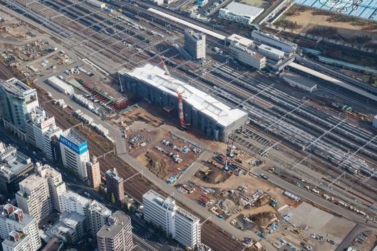 (写真1)建設工事が進む高輪ゲートウェイ(高輪GW)駅を南西方向の上空から見る。駅舎の左手、西口の一帯では土地区画整理事業による基盤整備が進む(画像提供:JR東日本)