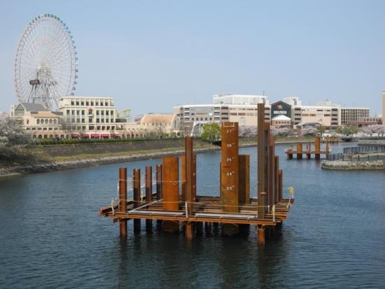 (写真1)JR桜木町駅側から見るロープウエーの支柱建設の現場(2020年4月3日時点)。右手に見える建物は、運河パークに隣接するショッピングセンター、横浜ワールドポーターズ。左手には、泉陽興業が運営するよこはまコスモワールド内の大観覧車、コスモクロック21が高々と立つ(写真:茂木俊輔)