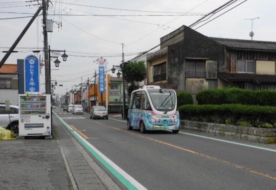 (写真1)町内を走行する自動運転バス。充電設備の設置場所は、1期運行の段階では「境シンパシーホールNA・KA・MA」の1カ所だけだったが、2期運行の段階での必要箇所は3カ所。増設については調整中だ(写真:茂木俊輔)