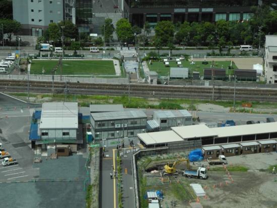 (写真3)「うめきた外庭SQUARE」の全景。右手、足元の見える黒っぽいビルが、梅田スカイビルだ。JR大阪駅側から現地に向かうときは、手前の歩行者用通路を右に折れ、地下に下ってJRの線路を潜り抜け、外庭SQUAREの2つのゾーンの間に出る(写真:茂木俊輔)