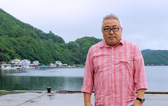阿曽浦漁港に立つ小川伸司氏。サバの養殖現場に向かうところ(撮影:筆者)