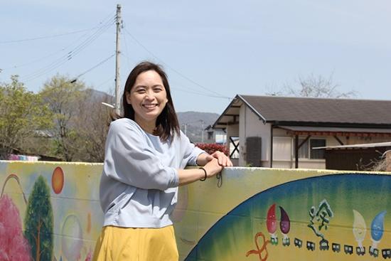 代表理事の榎本峰子さん。隣家との境に立つ塀に描かれた壁面アートの前で。