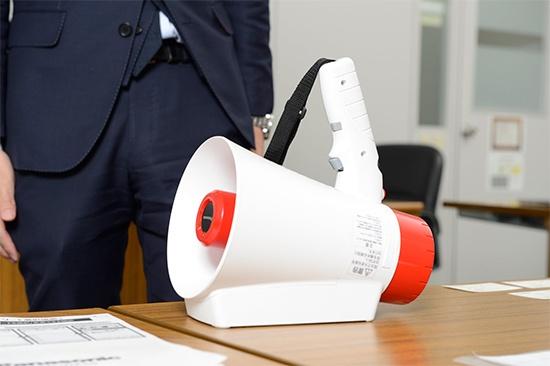 メガホンヤクは自立可能なため、再生ボタンをロックして置いておくことで、人がいなくても繰り返し拡声させることができる。
