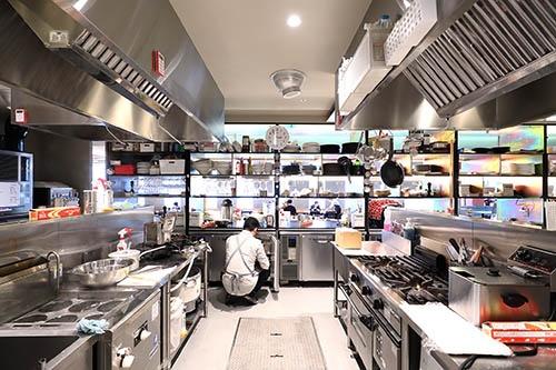キッチンスペースの様子。先ほどの店内写真をキッチン側から見た格好である。キッチンは大きく6つのブースに分かれており、それぞれにコンロや洗い場などの道具、ストックスペース(冷蔵庫)などが公平に設置されている(写真:北山宏一)