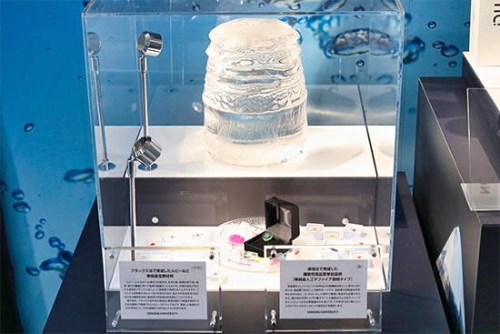 上段は、結晶の製造企業と共同開発している透明サファイアインゴット。下段はフラックス法およびその関連技術で育成した宝石結晶など。下段中央に見える緑色透明結晶は、信大の校章をデザインしたグリーンサファイアタックピン(写真撮影:山本真梨子)