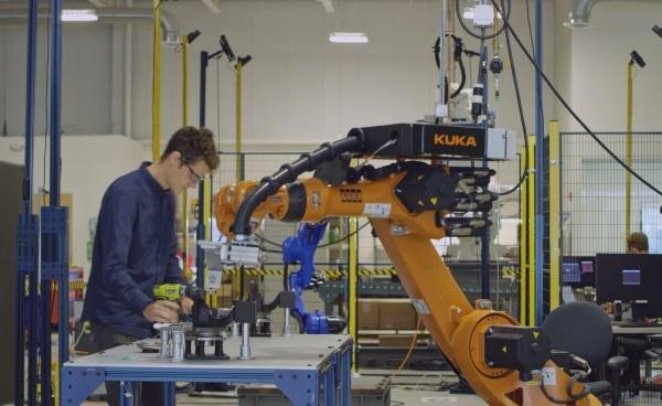 (写真1)作業台を挟んでロボットと人間が協働で作業を行う