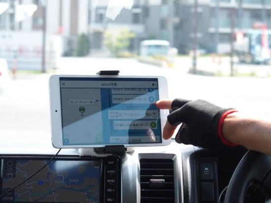 (写真2)伊都キャンパスを走るオンデマンド交通システム。利用者はキャンパス内の乗降ポイント(上)で車両の到着を待ち、ドライバーは配車オーダーが反映されたタブレット画面(下)の指示に従って運行する。