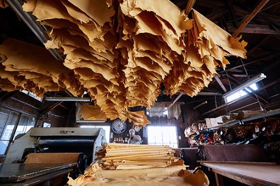 工場内、木組みの専用干し場になめした後の革を1枚ずつかけて自然乾燥させる(写真提供:山口産業)