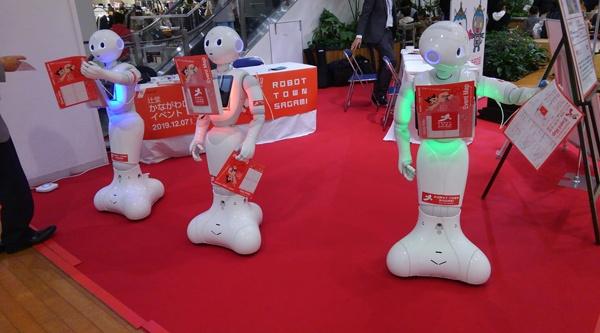 (写真1)藤沢市の大型ショッピングモールのイベント会場でチラシを配るPepperたち(写真提供:白井宏美氏)
