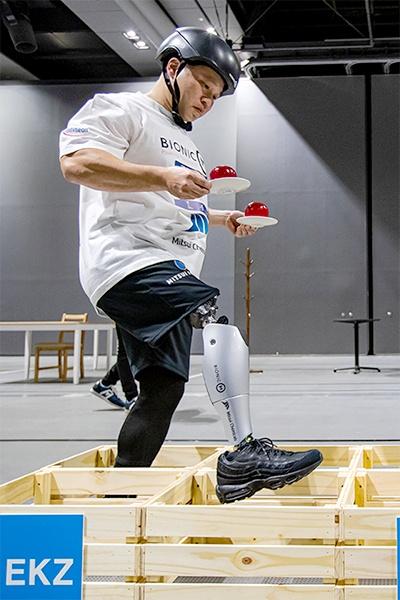 障害物を越えるパワード義足の滑らかな動きに注目が集まった。手に持つりんごはイミテーションでとても軽いため、より難しいタスクになっている(写真提供:BionicM ©Takao Ochi/Kanpara Press)