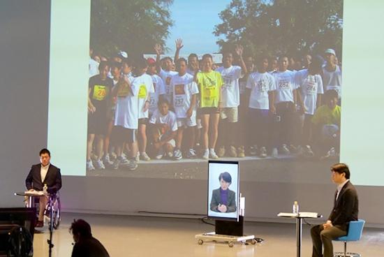 スクリーンの写真は、カンボジアで開催しているアンコールワット国際ハーフマラソンの参加者らと有森さん