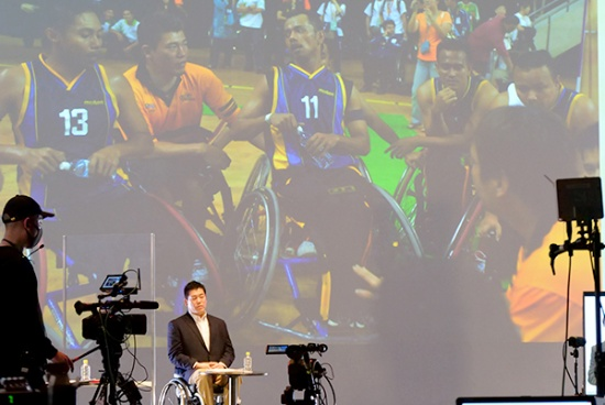 スクリーンは、マレーシアで初めて開催されたフェスピック(極東・南太平洋身体障害者スポーツ大会、現在はアジアパラ競技大会)でコーチとして選手を鼓舞する神保さん
