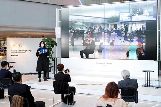 SCMプレイベント当日のオフライン会場の様子。前面のパネルには、イベント登壇者が持つタブレット機の画面イメージが投影されている。オフラインの参加者とオンラインの参加者の情報が統合して表示される