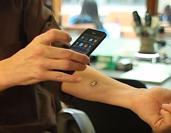 (写真1)ジョン・A・ロジャース教授が開発した汗の成分を読み取るパッチ型センサー。スマートフォンでデータを読み取る仕組み(出典:米ノースウエスタン大学のYouTubeより)