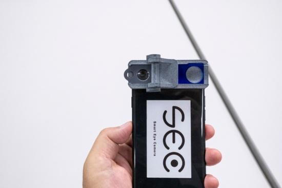 スマホに装着した状態のSEC。現在はiPhone 7/8/SE(2代目)に対応だが、Android対応デバイスとアプリも開発中。価格はスマホとアプリがセットで20万〜30万円ほど(写真:小口正貴)
