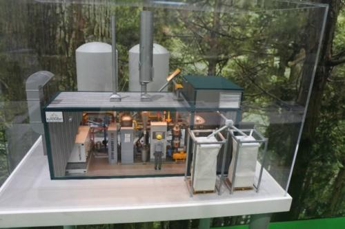 図3●三洋貿易が見本市で展示したブルクハルト製の木質ペレット・ガス化熱電併給装置。手前の2つの白い容器が今回の出火元になったと推測されている