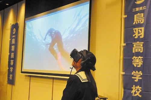 記者会見の会場でVR映像を紹介する三重県立鳥羽高等学校の生徒。スクリーンには、ゴーグルで見えている映像を映し出している
