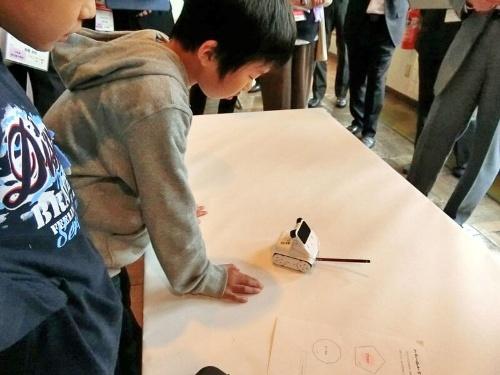 鉛筆をくくり付けたロボット教材「Codey Rocky」(ケニス)をプログラムで走らせると、紙の上に正多角形が描かれた