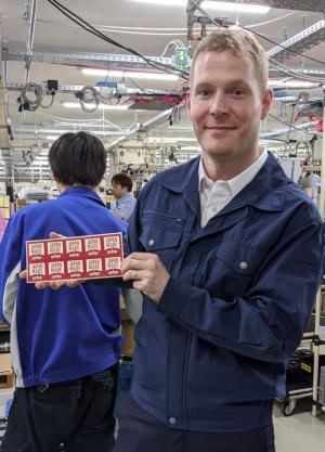「JAPAN MADE & SUPPORT」シールを手にするベネット社長。全ての米沢生産品にこのシールが貼られる