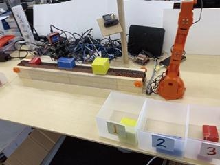 ベルトコンベヤー上の荷物を分析して箱に仕分けするロボット