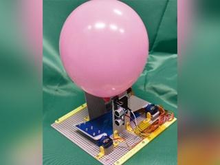 風船を下からたたき上げる「風船打ち出し器」、打ち出し後は自動で最初の状態に戻される