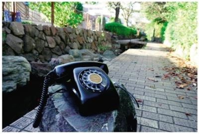 図1 屋外で利用中の黒電話