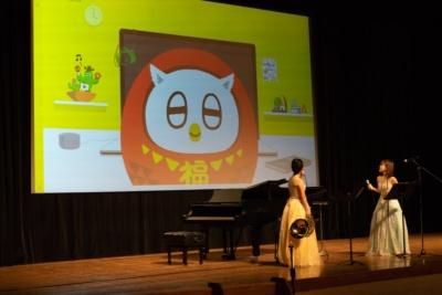 ステージのスクリーンに登場したAIアシスタント「ふくまろ」。コンサートの演奏者は、ホルンの相原結さん(左)とフルートの上塚恵理さん(右)
